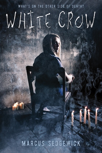US cover of White Crow with girl in dark room, sitting in a chair with her back towards the viewer.