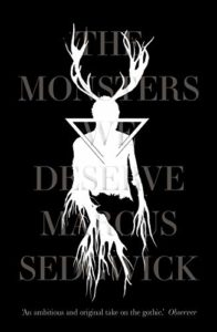 Paperback cover of The Monsters We Deserve showing a man with angels in white silhouette on black